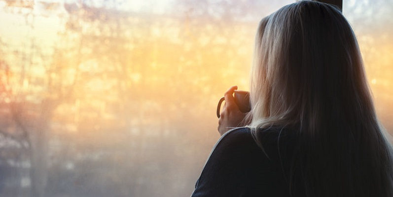 Woman With Coffee Peering Out Window
