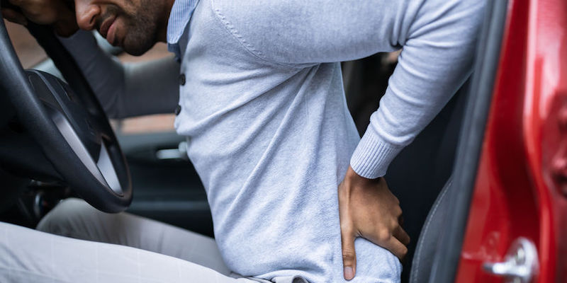 Driver Sitting in a Car Having Back Pain After an Accident